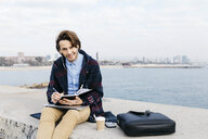 Spain, Barcelona, portrait of man sitting at the sea taking notes - JRFF02524