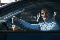 Portrait of smiling businessman driving car - JRFF02536