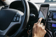Close-up of man with tattooed hand driving car using cell phone as navigation system - JRFF02539