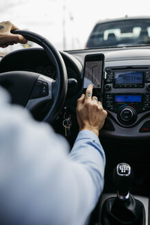 Close-up of man with tattooed hand driving car using cell phone as navigation system - JRFF02542