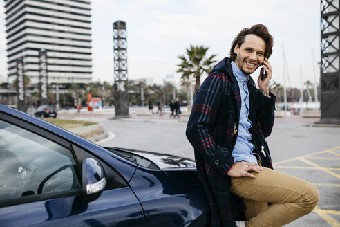 Spain, Barcelona, smiling man on cell phone outside car in the city - JRFF02545