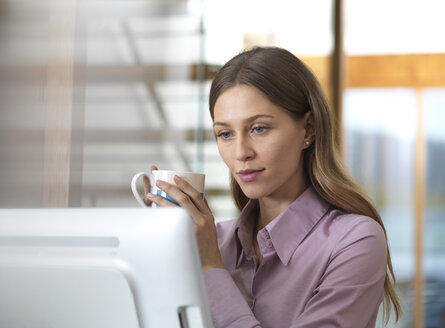 Businesswoman in office holding cup looking at PC - ABRF00260