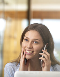 Portait of smiling businesswoman on cell phone in office - ABRF00266