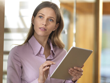 Businesswoman using tablet in office - ABRF00269