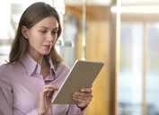 Businesswoman using tablet in office - ABRF00272