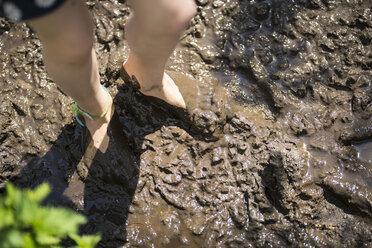 Children's bare feet sunken deep in brown mud - SBOF01700