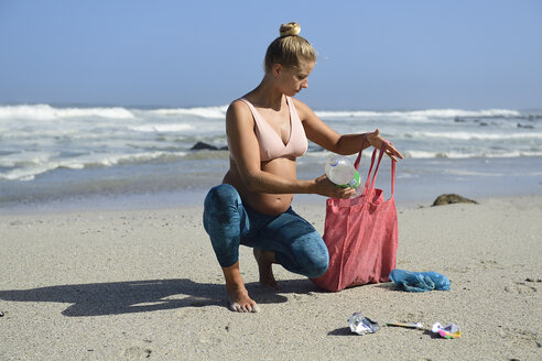 Pregnant woman cleaning the beach from plastic waste - ECPF00361
