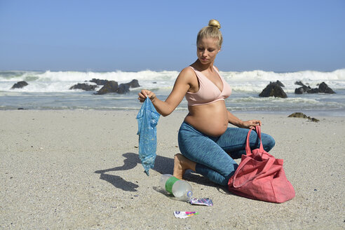 Pregnant woman cleaning the beach from plastic waste - ECPF00367