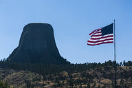 USA, Wyoming, US flag before the Devils Tower National Monument - RUNF01053
