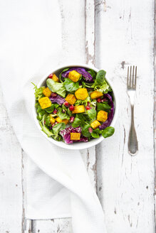 Mixed salad with roasted tofu, red cabbage, pomegranate seeds and curcuma in bowl on white wood - LVF07738