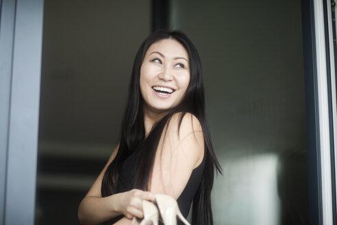 Junge Frau im schicken Kleid mit High Heels am Fenster - SGF02228