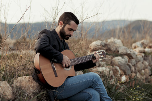 Male musician with beard playing the guitar in the countryside - LOTF00059