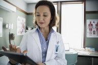 Doctor using digital tablet in examination room - HEROF14859