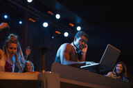 DJ at laptop on stage in nightclub - HEROF14895
