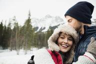 Couple hugging below snowy mountain - HEROF14961