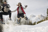 Couple jumping in snowshoes below snowy mountain - HEROF14982