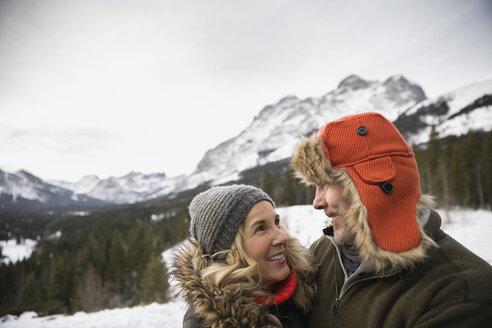 Couple smiling below snowy mountains - HEROF14985