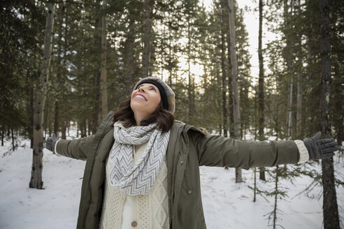 Exuberant woman with arms outstretched in snowy woods - HEROF14991
