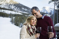 Couple drinking wine with snowy mountains in background - HEROF15045