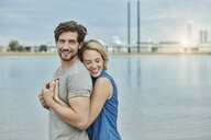Happy young couple hugging at the riverbank - RORF01672