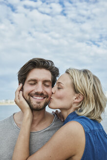 Happy young couple kissing on the beach - RORF01681