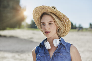 Portrait of young woman with headphones and straw hat on the beach - RORF01687