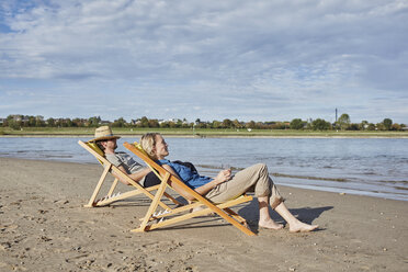 Young couple in deckchairs relaxing at the riverbank - RORF01708