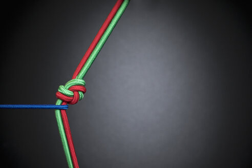 Blue rope tugging at red and green rope knotted in teamwork, unity - HEROF15055