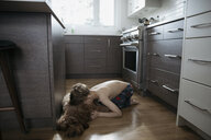 Affectionate bare chested boy cuddling dog laying on kitchen floor - HEROF15112