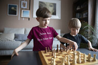 Brothers playing chess in living room - HEROF15118