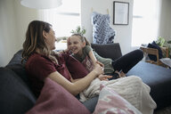 Affectionate mother and daughter bonding, talking on living room sofa - HEROF15124
