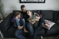 Affectionate, playful father tickling daughters on living room sofa - HEROF15127