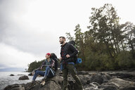 Couple hikers on rocks on rugged beach - HEROF15145