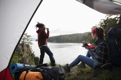Couple eating, camping on cliff overlooking ocean - HEROF15148
