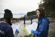 Eco-friendly female scientists with paperwork on beach - HEROF15160