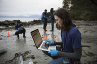 Eco-friendly female scientist with laptop on beach - HEROF15166