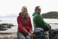 Carefree active senior couple backpacking, resting on rugged beach - HEROF15178
