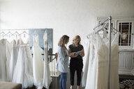 Bridal shop owner helping bride with digital tablet shop for wedding dress - HEROF15199