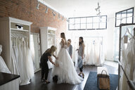 Bride and friends at wedding dress fitting in bridal boutique - HEROF15205