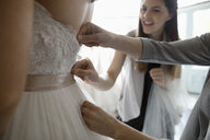 Bride and friends at wedding dress fitting in bridal boutique - HEROF15208