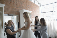 Bride and mother at wedding dress fitting in bridal boutique - HEROF15211