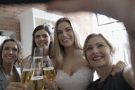 Bride, mother and friends taking selfie with champagne at wedding dress fitting at bridal boutique - HEROF15217