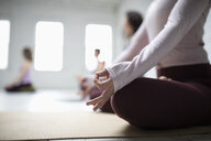 Close up woman practicing lotus position meditation with hand in gyan mudra in yoga class - HEROF15223
