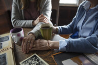 Affectionate senior mother and daughter holding hands, drinking coffee and looking at photo albums - HEROF15229