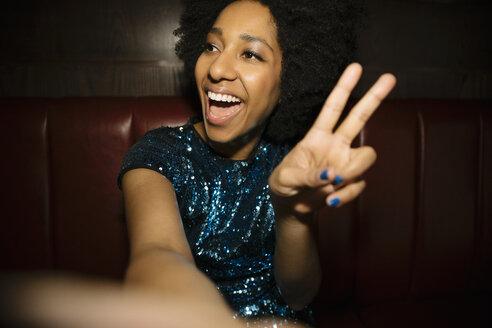 Confident, cool female millennial taking selfie, gesturing peace sign - HEROF15295