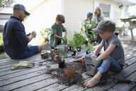 Family potting plants on deck - HEROF15322
