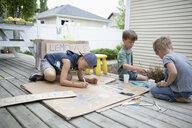 Brothers painting lemonade stand in back yard - HEROF15331