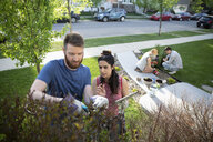 Couples with digital tablet gardening, doing yard work in front yard - HEROF15337