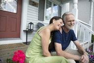 Affectionate senior couple relaxing on front stoop - HEROF15346