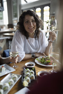 Woman drinking wine and eating sushi with friends at restaurant - HEROF15418